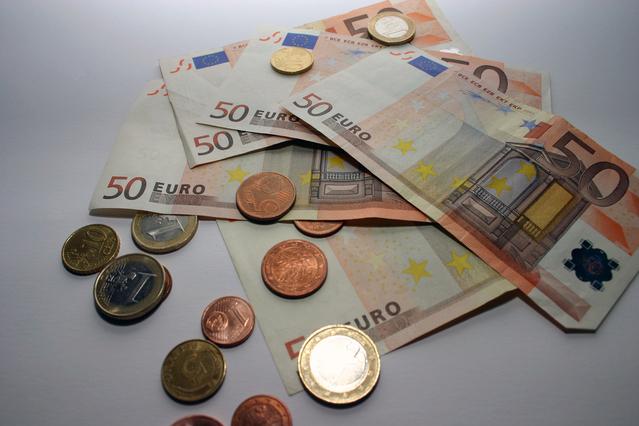 hromádka mincí a bankovek na bílém podkladu